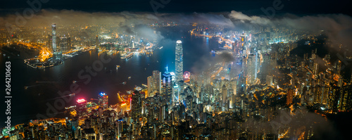 Wall mural Panorama aerial view of Hong Kong City skyline at night over the clouds