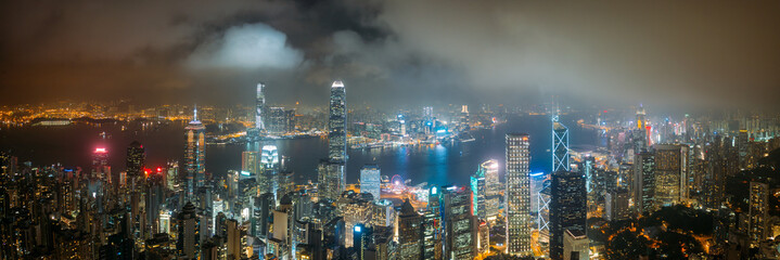 Wall Mural - Panorama aerial view of Hong Kong City skyline at night over the clouds