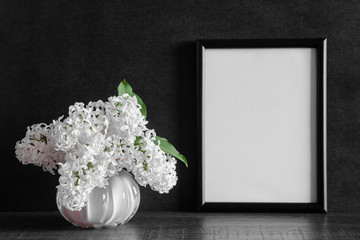 Fresh bouquet of white lilac flowers in vase on shelf at black wall. Condolence concept. Empty place for emotional, sentimental text, quote or photo in frame. Front view.