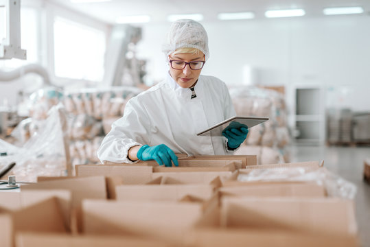 Young Caucasian employee in sterile uniform holding tablet and counting products in boxes. Food factory interior.