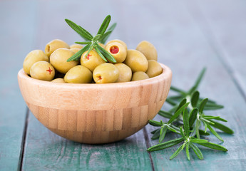 Green olives with rosemary on a wooden table