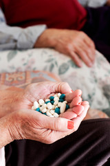senior woman with a pile of pills in his hand
