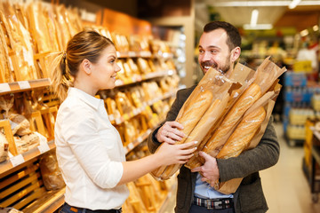 Couple is choosing bakery in bread department in the supermarket