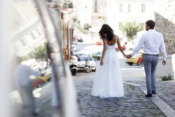 Back view of a romantic couple of a newlyweds walks on the old street greece. Wedding in greece.