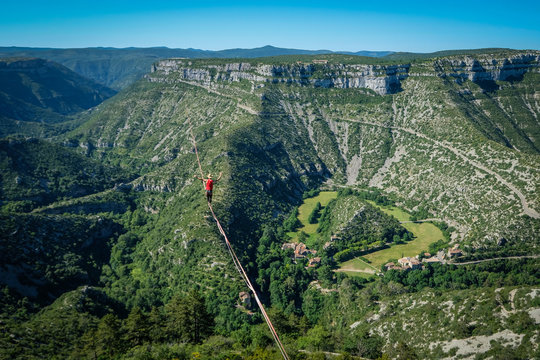 a man walking on the longest slackline ever in Navacelles circus (world humanity patrimony) at 300 meters high, Occitanie, Navacelles, France