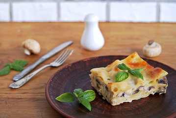 Portion of lasagna with chicken, mushrooms and mozzarella cheese on a brown clay plate. Italian сuisine. Selective focus.