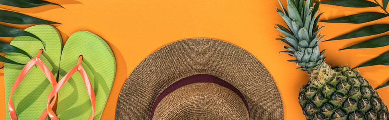 panoramic shot of pineapple, tropical leaves, green flip flops and brown straw hat on orange...