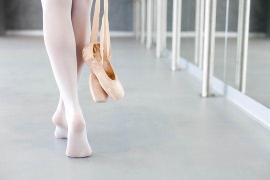 Ballerina takes off ballet pointe shoes. Girl is finishing workout and going barefoot in dance class room. Close up of legs.