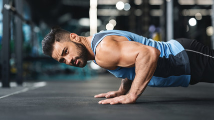 Wall Mural - Strong caucasian guy making plank or push ups exercise,