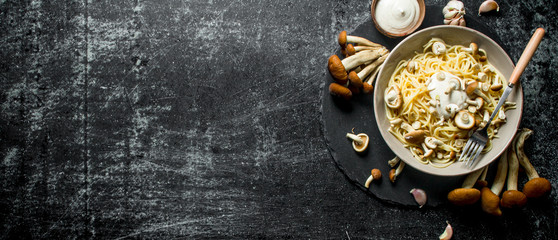 The pasta with the sauce in a bowl and fresh mushrooms.