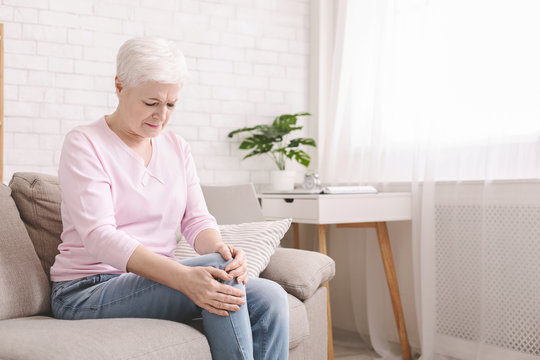 Senior woman suffering from pain in leg, massaging her knee