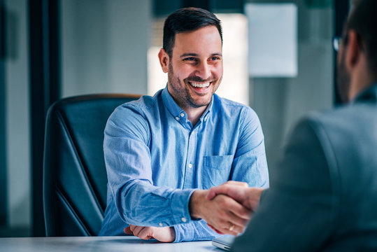 Two smiling businessmen shaking hands while sitting at the office desk.