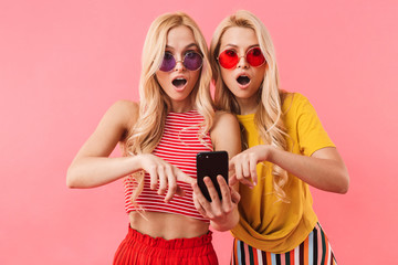 Shocked blonde twins in sunglasses using smartphone