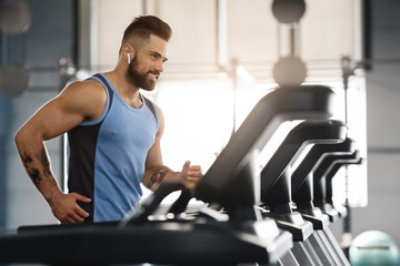 Wall Mural - Young handsome man running on treadmill at gym