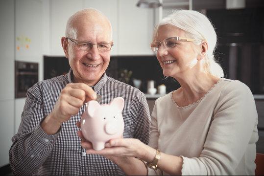 Senior couple puts the coin into the piggybank