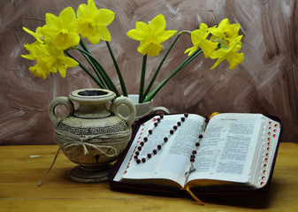 daffodils in a clay bug on a wooden table, open Bible