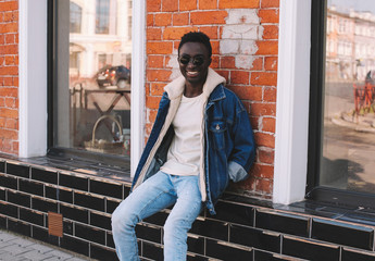 Wall Mural - Stylish happy smiling african man wearing jeans jacket sitting on city street over brick wall background