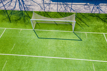 Aerial view of Sport concept of synthetic football or soccer field space with gates and grass background texture and empty space for copy