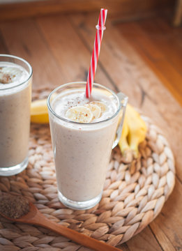 Close-up of banana and flax seeds smoothie in a glass on wooden background