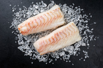 Raw Norwegian skrei cod fish filet as top view on crashed ice on a black board with copy space