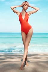 Spoed Foto op Canvas womenART Beautiful sexy woman in red swimwear on the beach