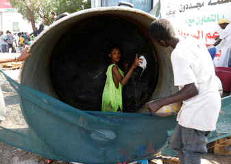 A Sudanese volunteer washes a huge cauldron used for cooking food for protesters outside the defence ministry compound in Khartoum