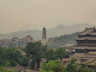 A polluted city of China, in the nearby of a Great Wall, a thick fog covers everything. Visibility is really low. Mountains barely visible. Tall temple in the middle. Traditional Chinese architecture