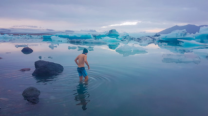 Young man getting into the water of Glacier lagoon. Man wearing only swimming shorts and a hat. Ice bergs drifting in the lagoon. Cold temperatures for ice swimming. Calm surface of the water.