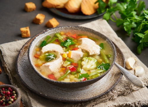 Homemade chicken soup with vegetables, broccoli on dark brown background, side view.