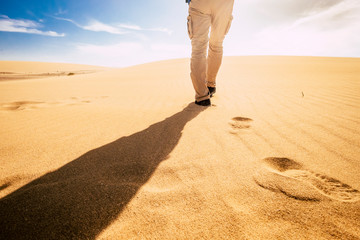 Travel and explore people concept with man viewed from back walking in tha sand of the desert dunes alone under the sunset - summer holiday vacation and nature outdoor in scenic place