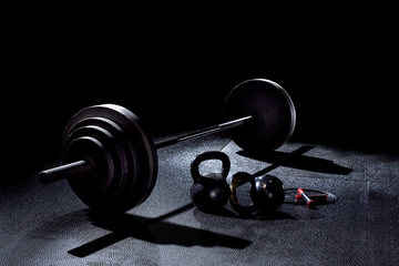 BACK LIT image of 365 pound weight on barbell with kettle bells and jump rope on gym floor