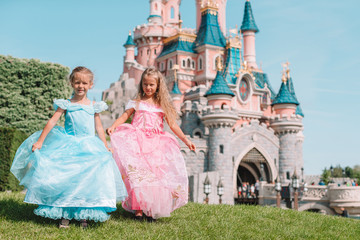 Little adorable girls in beautiful princess dress at fairy-tale park