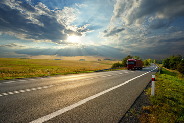 Fotobehang - Red truck driving on the asphalt road in rural landscape at sunset with dramatic clouds