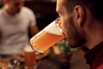 Close up of man drinking beer in a bar.