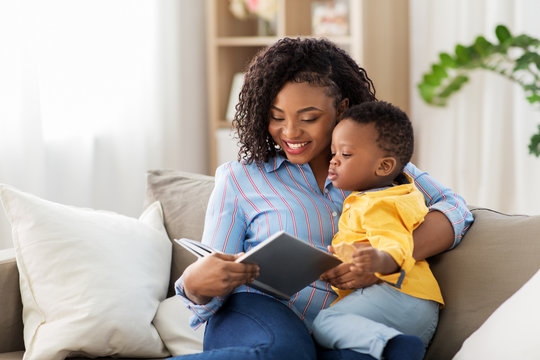 childhood, kids and people concept - happy african american mother with book and her baby son at home