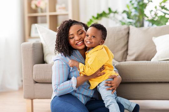 childhood, kids and people concept - happy african american mother with her baby son at home