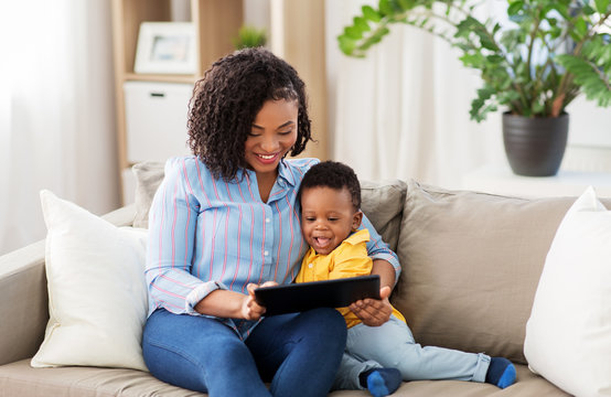 family, motherhood and technology concept - happy african american mother using tablet computer with little baby son at home