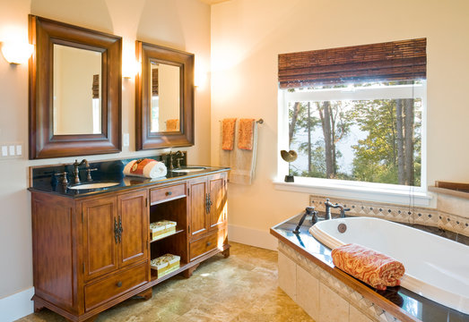 Luxury master bath bathroom with wood cabinets, tile floor and bathtub surround, soaking tub and twin sinks with high quality fixtures in traditional upscale home interior