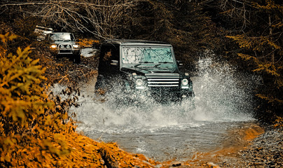 Mud and water splash in off-road racing. Off road sport truck between mountains landscape. Expedition offroader. Tracks on a muddy field. Road adventure. Adventure travel. Wall mural