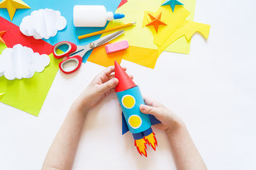 hands of the child make a paper craft rocket. Cosmos clouds and stars colored paper. The creative...