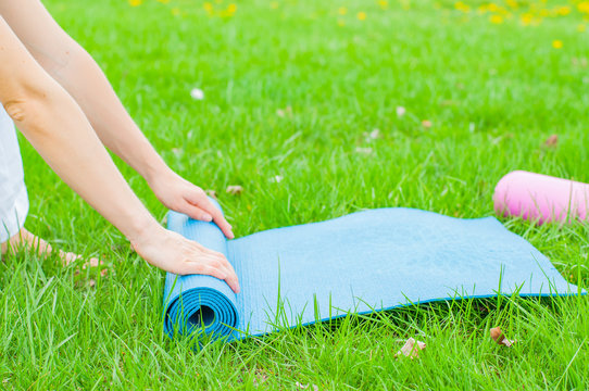 Woman is folding yoga or fitness mat on the grass. Healthy life, keep fit concepts.