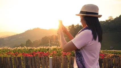 Asian female tourists are using a mobile phone to take pictures of the sunset scenery.