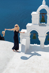 blond woman next to a Santorini bell tower in Oia