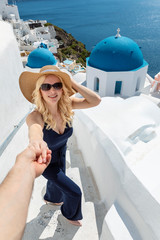 blond woman wearing a hat, standing on stairs with her husband holding her hand and the famous blue church domes in the background