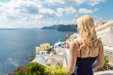 blond woman enjoying the caldera view in Oia on Santorini with her back to the camera