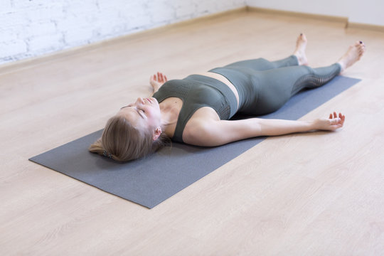 Woman laying on mat in relaxing pose on the floor. Yoga class, the shavasana.