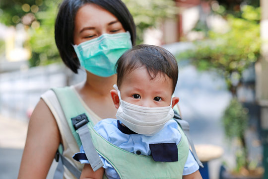 Close up mom carrying her baby by hipseat with wearing a protection mask against air pollution in the city.