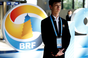 A volunteer stands next to a Belt and Road Forum (BRF) logo at the China National Convention Center, in Beijing