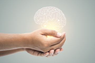 Man holding brain illustration against gray wall background. Concept with mental health protection and care. Wall mural