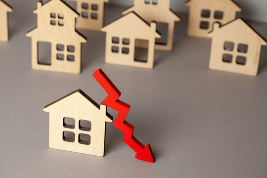 Arrow down and many houses. Falling real estate prices market. Buying and selling house